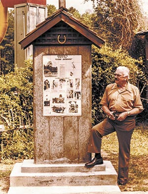 Artist and Serial Entrepreneur Clyde Gray stands at Heritage Village next to a monument preserving the day an outhouse took wing in Tyler County. Your (much younger) editor shot the top left and right photos on the monument in 1976.