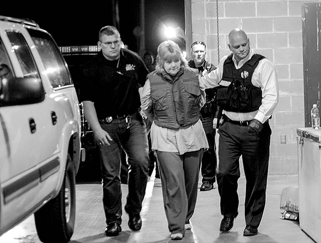 Letha Westfall, center in photo, is escorted into Tyler County Justice Center by Tyler County Sheriff Bryan Weatherford (right) after being arrested, along with family members Paul, Kristen and Cameron Westfall, after being indicted for the Maddox murders.