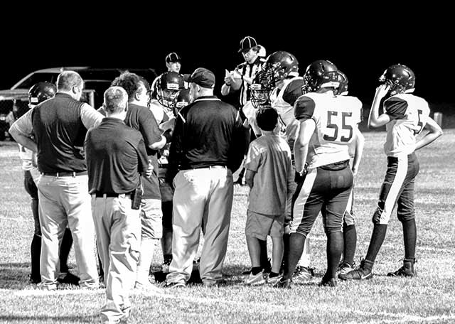 Coach Jeremy Wooten, pictured in center, discusses strategy with his 2017 Yellowjacket football team. Wooten is pleased with his district competitors for the 2018 season. (JANA RAYBURN | TCB )