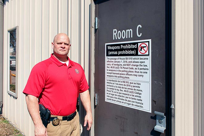 "Tyler County Sheriff Bryan Weatherford places a ""Weapons Prohibited"" sign at Tyler County Nutrition Center (Jim Powers Photo)"