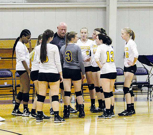 Coach DeWayne Armstrong gives the Lady Jacket volleyball team some pointers.  The team is preparing for their district opener at Apple Springs on Friday, Sept. 8 at 4:30 p.m. (Jana Rayburn.)