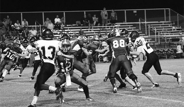 Colmesneil Bulldogs #12 Cole Johnson and teammates defend their turf against a pack of Hull-Daisetta Bobcats Friday night at Taylor Field. (Chris Edwards Photo)
