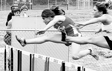 Jaymee Broussard clears a hurdle at a track meet. (Chance Bailey Photo)