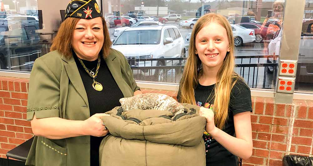 Michelle Scuito, Veterans Career Adivsor for the VA and Sergeant-at-Arms of the American Legion, Lufkin Post #113, accepts a clothing donation from Elysabeth Bryan.