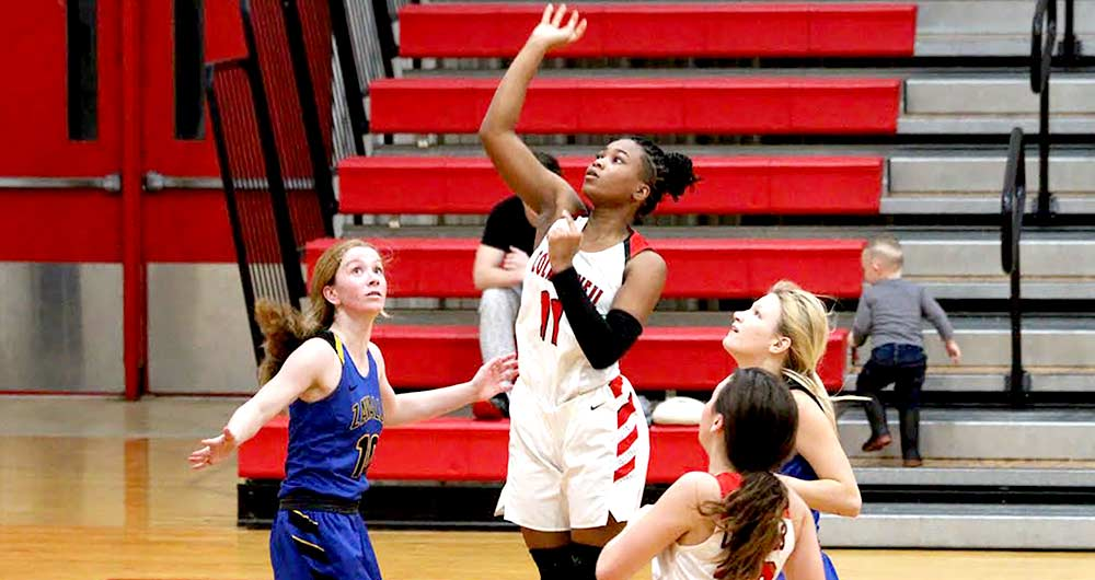 Senior Lexi Washington goes up to shoot for the Lady Dogs. (PHOTO COURTESY OF COLMESNEIL ISD YEARBOOK STAFF )